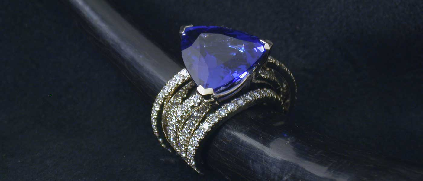 David Mann — Bijoutier à Liège - Bague fils de diamants brillants sertis d'une tanzanite en triangle et or blanc