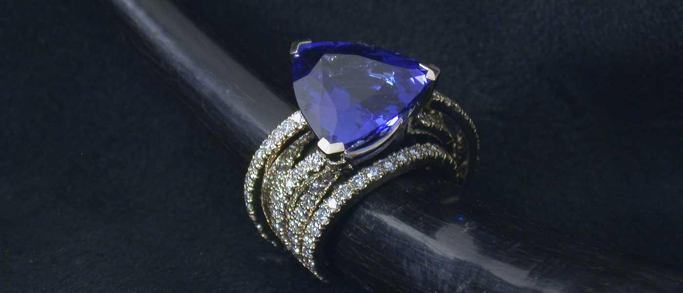 David Mann — Bijoutier à Liège - Bague fils de diamants brillants sertis d'une tanzanite en triangle et or blanc